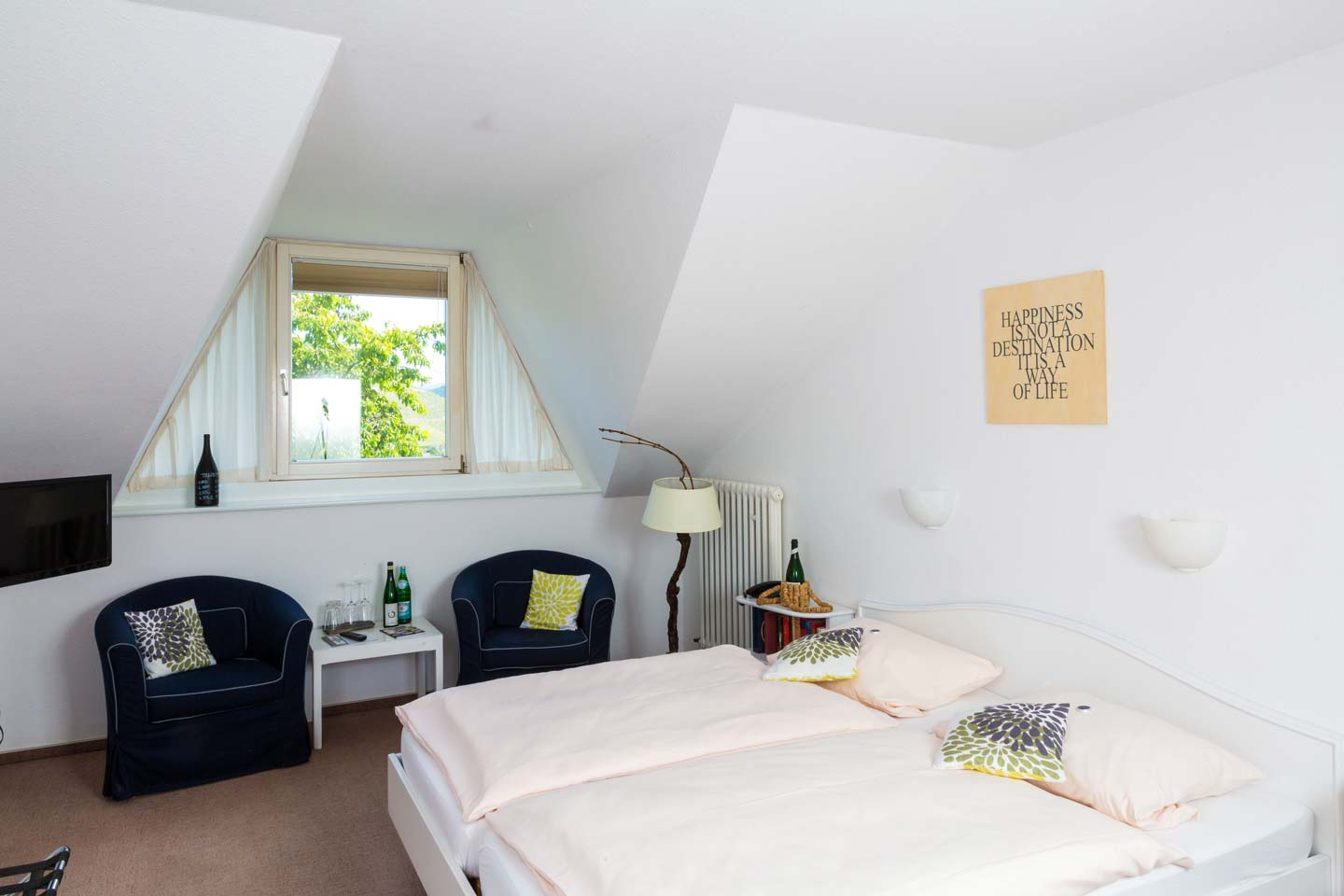 Attic room with double bed and armchairs