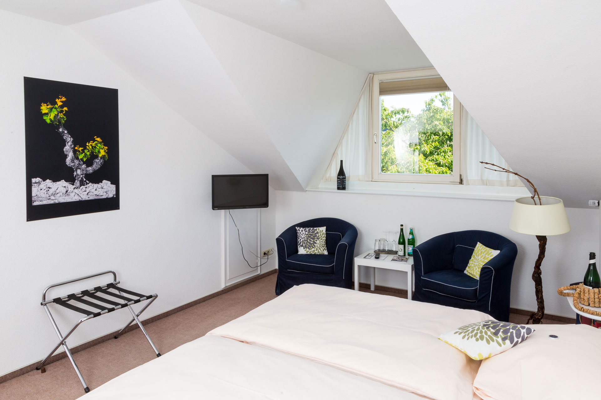Attic room with bed and two armchairs