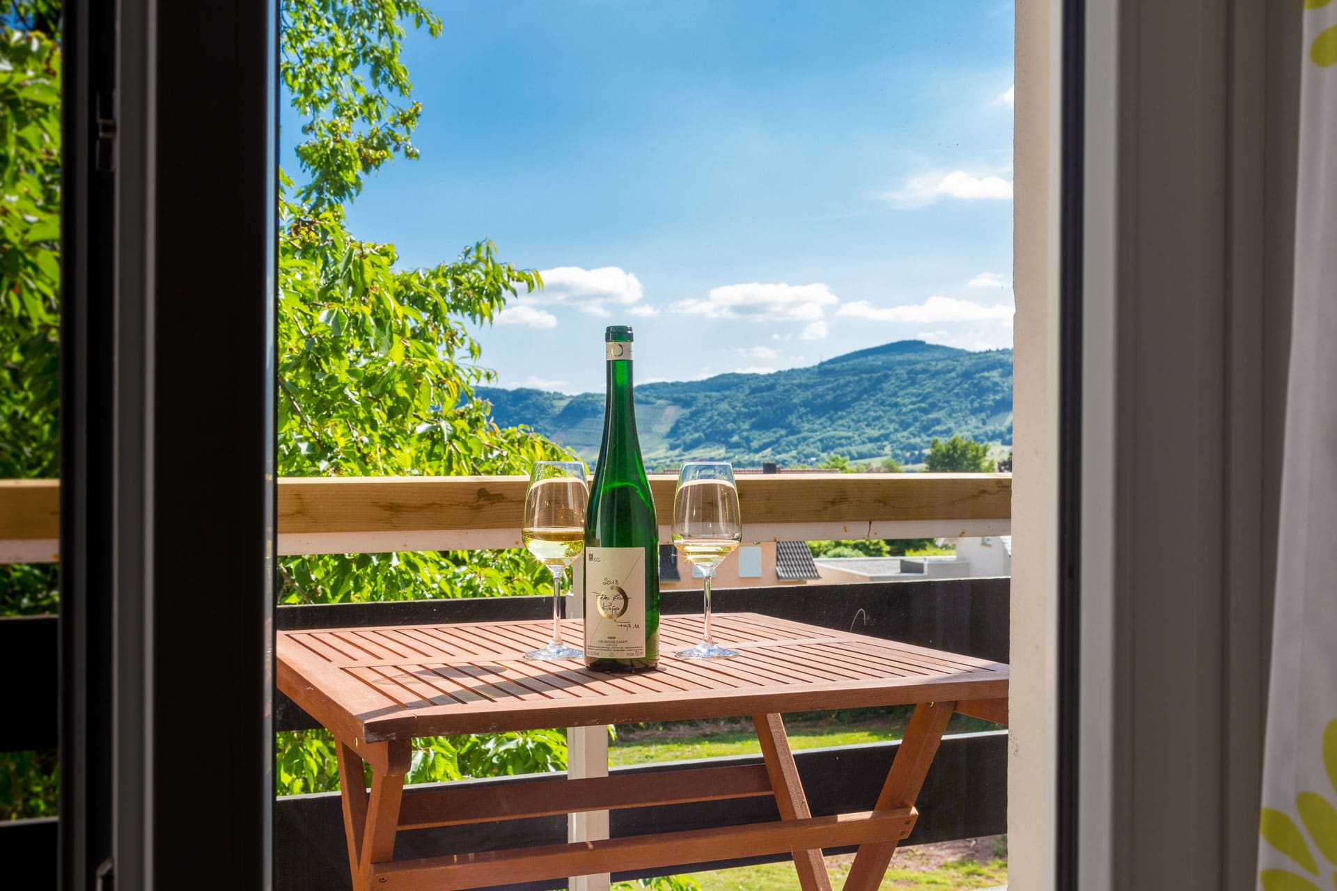 Bottle of wine and glasses on a table on a balcony