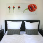 Double bed and painting with flowers on the wall