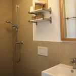 Hotel bathroom with shower, toilet, and mirror