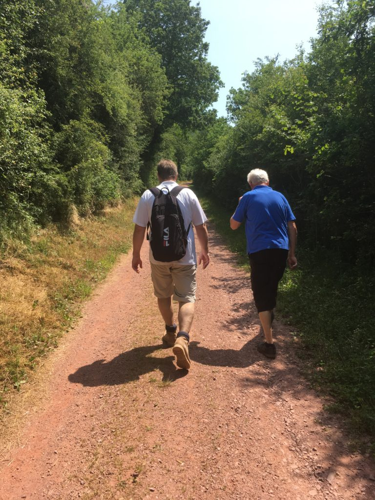 Two people walking along a dirt path